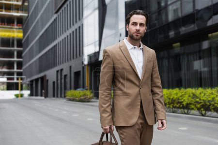 Photo for Young businessman in suit holding leather bag on urban street - Royalty Free Image