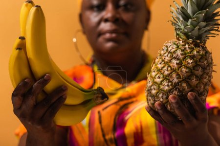 bananas and pineapple in hands of blurred middle aged african american woman on orange