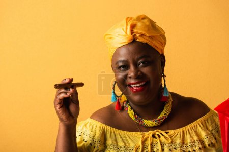 smiling middle aged african american woman in yellow turban and blouse holding cigar on yellow