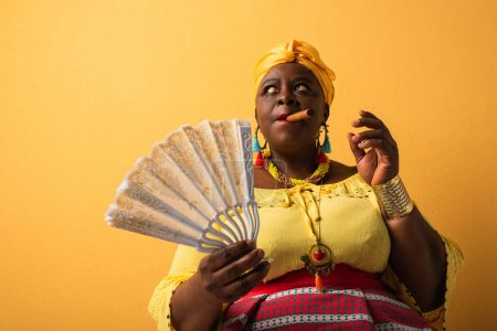 middle aged african american woman in yellow turban and bright clothes holding fan and smoking cigar on yellow
