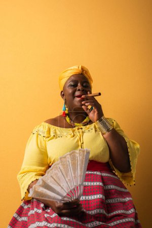 middle aged african american woman in bright clothes sitting with fan and smoking cigar on yellow