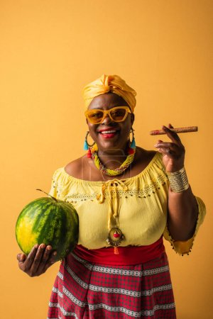 smiling middle aged african american woman in sunglasses holding watermelon and cigar on yellow