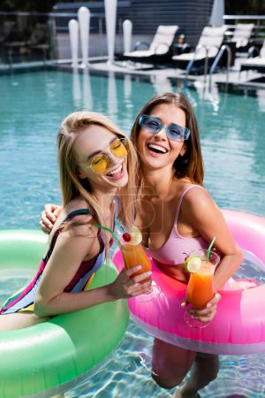 excited woman in sunglasses and swimsuits relaxing with cocktails in pool