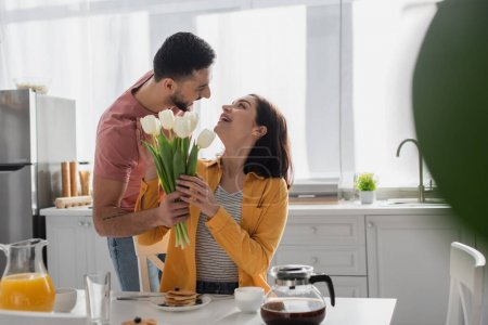 young man presenting bouquet of flowers to girlfriend sitting on table in kitchen