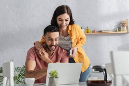 Photo pour Souriant jeune femme tenant téléphone portable et toucher les mains avec petit ami travaillant avec ordinateur portable à la maison - image libre de droit