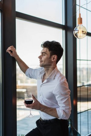 Photo for Elegant man in white shirt holding glass of red wine while standing near window - Royalty Free Image