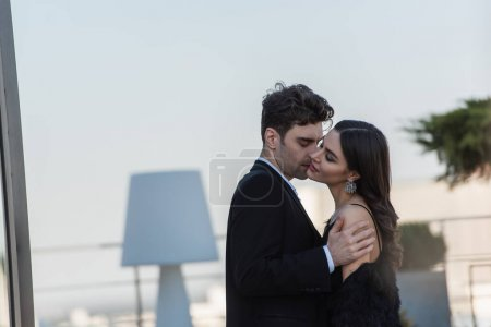 Photo for Man hugging smiling woman in dress on terrace of restaurant - Royalty Free Image
