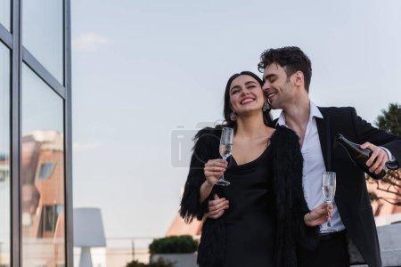 homme heureux tenant bouteille de champagne près de petite amie gaie en fausse veste de fourrure