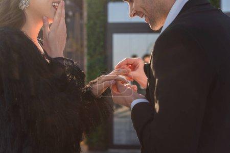 Photo pour Vue partielle de l'homme portant anneau sur doigt de petite amie heureuse à l'extérieur - image libre de droit