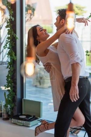 Photo for Excited man in shirt and happy woman in slip dress hugging in restaurant - Royalty Free Image