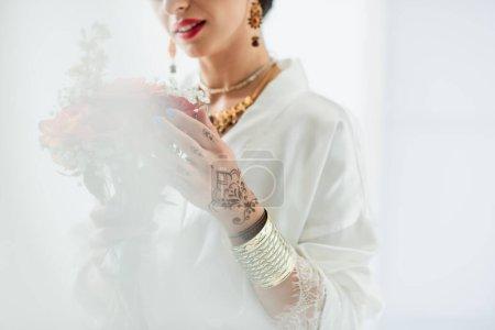 abgeschnittene Ansicht der indischen Braut mit Blumenstrauß auf weißem Grund