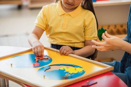Ausgeschnittene Ansicht eines Mädchens, das Erdkartenpuzzle in der Nähe eines Lehrers in der Montessori-Schule kombiniert