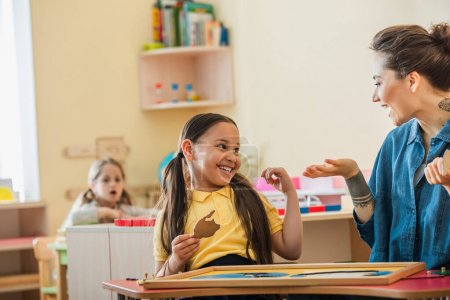 Lehrerin gestikuliert in der Nähe lachendes asiatisches Mädchen mit Puzzleteil während des Unterrichts