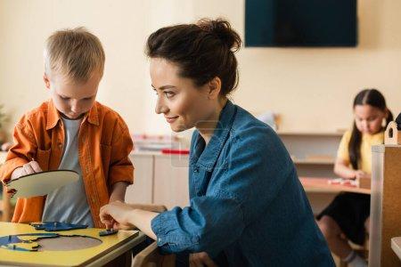 Lächelnder Lehrer, der einen Jungen ansieht, der Erdkartenpuzzle in der Nähe verschwommener asiatischer Mädchen kombiniert