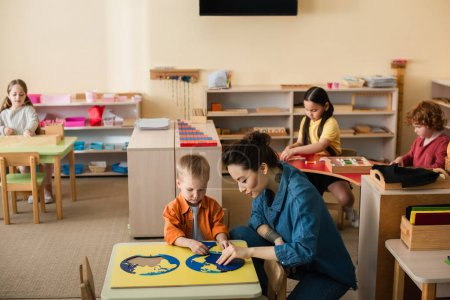 teacher with boy combining earth map puzzle near kids playing educational games