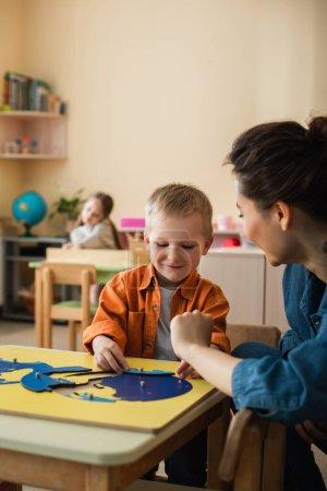 fröhlicher Junge kombiniert Erdkartenpuzzle in der Nähe von Lehrer und verschwommenem Mädchen