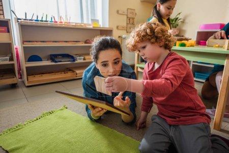 Lehrer und Junge spielen in Montessori-Schule mit Holzbrettern auf dem Boden