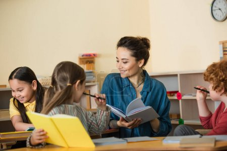 happy teacher holding textbook near multiethnic children in classroom