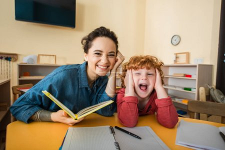 excited kid with open mouth touching head near cheerful teacher with book