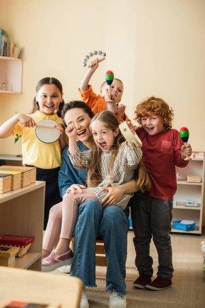 fröhliche multiethnische Kinder mit einem Lehrer, der im Klassenzimmer Musikinstrumente spielt