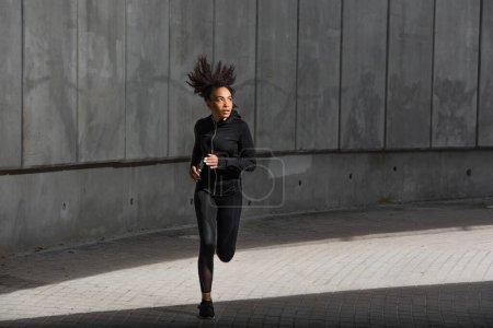 Photo pour Jeune sportive afro-américaine courant près d'un immeuble dans une rue urbaine - image libre de droit