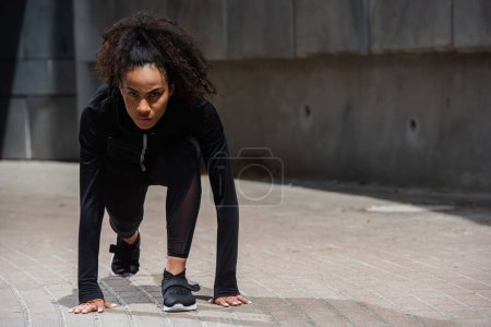 Young african american runner looking at camera while standing in starting pose outdoors