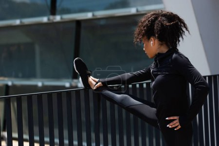 Photo for Young african american sportswoman in earphone warming up near bridge - Royalty Free Image