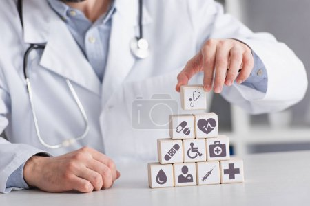 Photo for Cropped view of blurred doctor in white coat making pyramid of cubes with medical symbols - Royalty Free Image
