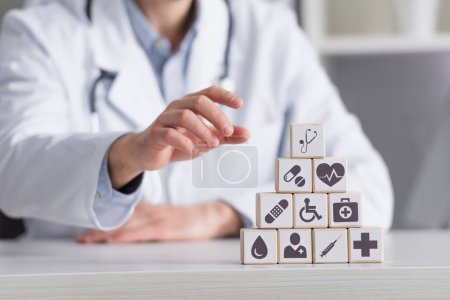 Photo for Pyramid of cubes with medical signs near blurred physician in white coat, cropped view - Royalty Free Image