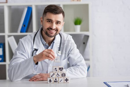 Photo for Physician in white coat smiling near pyramid of cubes with medical icons on desk - Royalty Free Image