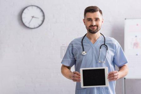 heureux médecin en uniforme bleu tenant tablette numérique avec écran blanc