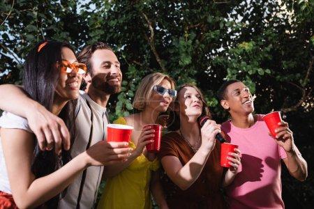 Photo pour Joyeux amis multiethniques embrasser et chanter karaoké pendant la fête d'été - image libre de droit