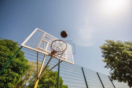 Vue à angle bas du ballon de basket près du cerceau sur l'aire de jeux à l'extérieur