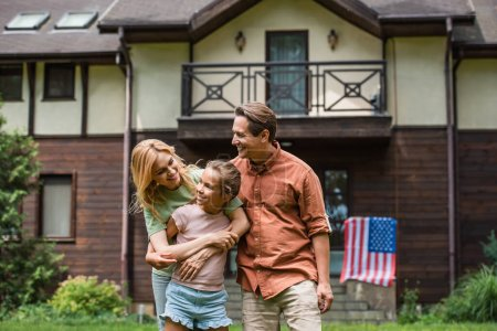 Smiling family hugging daughter near blurred american flag on vacation house