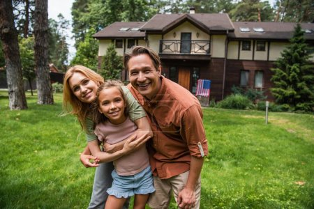 Positive man looking at camera while wife hugging daughter outdoors