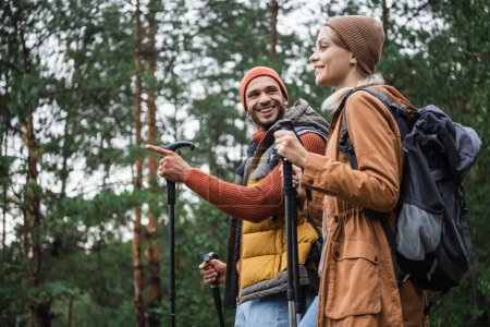 happy man pointing away with finger while looking at girlfriend with hiking sticks in forest