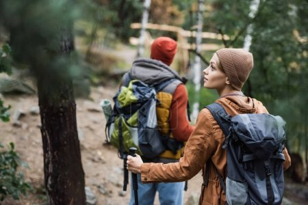 young woman with backpack looking away near man trekking in forest on blurred background