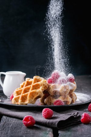 Photo for Belgian waffles with raspberries and sieving sugar powder, served with jug of milk on vintage metal tray with textile napkin over old wooden table. Dark rustic style. - Royalty Free Image