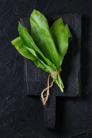 Photo for Bunch of fresh ramson on wooden chopping board over black textured background. Top view - Royalty Free Image