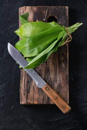 Photo for Bunch of fresh ramson on wooden chopping board with vintage knife over black textured background. Top view - Royalty Free Image