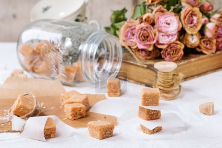 Photo for Fudge candy and caramel on baking paper and in glass jar, served over white tablecloth with bouquet of dry pink roses and thread for gift making. See series - Royalty Free Image