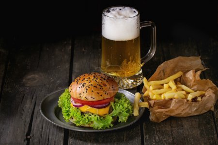 Photo for Fresh homemade burger with in old metal plate with french fries potatoes in baking paper, served with glass of cold lager beer over old wooden table with dark background. Dark rustic style. - Royalty Free Image