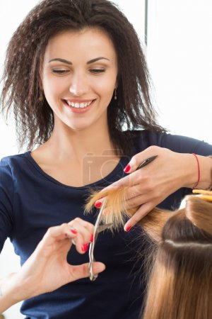 Smiling female hairdresser cutting client hair tips
