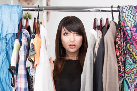 Photo for Portrait of young confused woman in front of a wardrobe full of clothes. Nothing to wear concept - Royalty Free Image