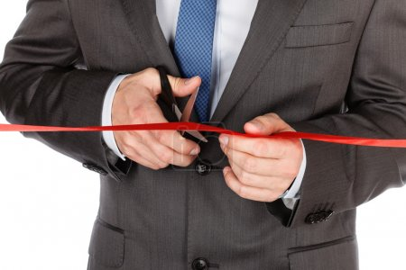 Businessman in suit cutting red ribbon with pair of scissors iso