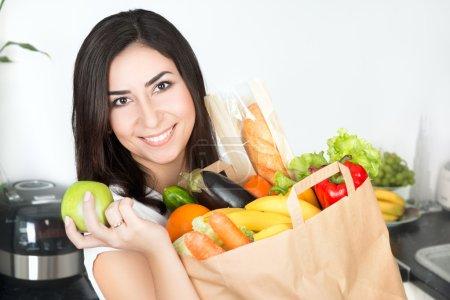 Photo pour Verticale de jeune belle femme de brunet restant sur sa cuisine avec juste livré grand sac en papier plein de nourriture végétarienne et retenant la pomme verte - image libre de droit