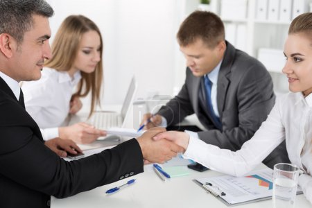 Photo for Businessman in suit shaking woman hand with their colleagues acting at background. Partners made deal and sealed it with handclasp. Formal greeting gesture - Royalty Free Image