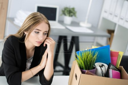 Young dismissed female worker in office sitting near carton box