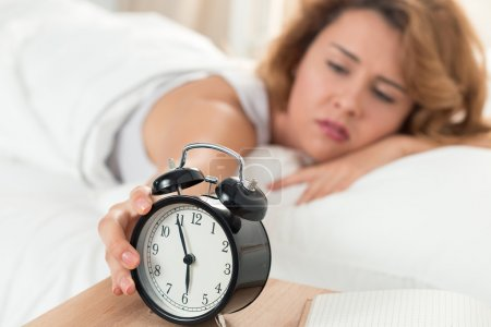 Young sleepy woman trying to turn off the alarm clock
