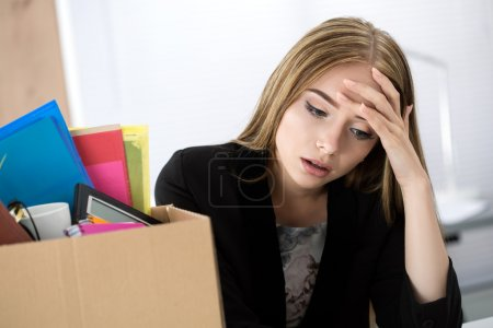 Young dismissed female worker sitting near the carton box with h